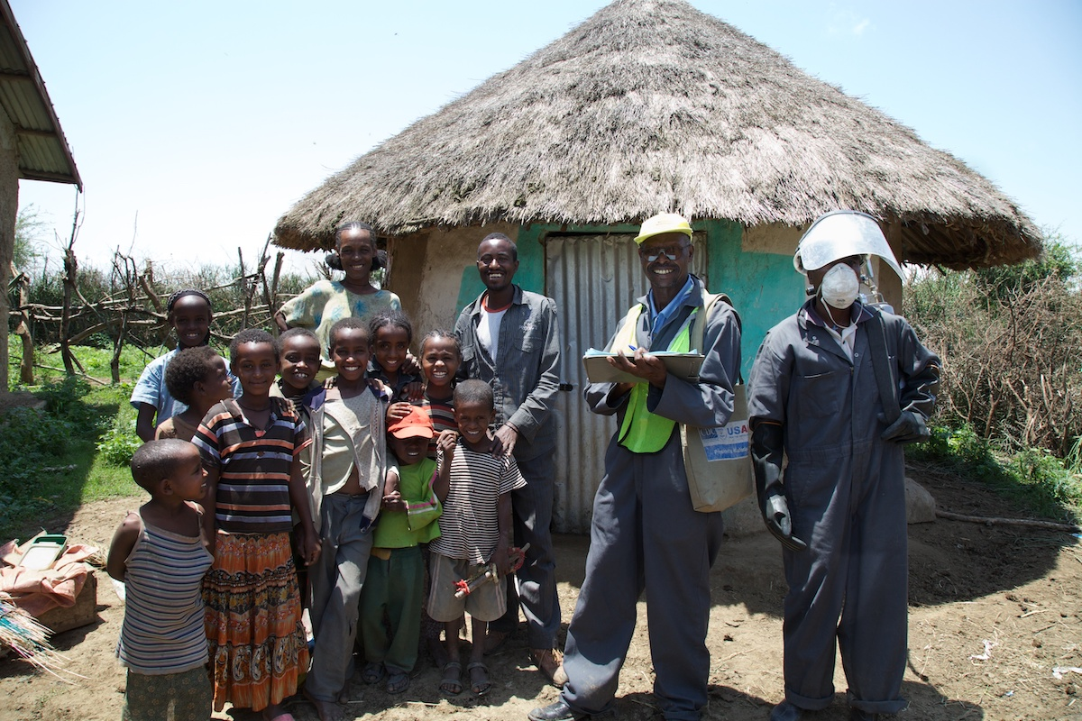 IRS spray campaign team with villagers outside their home, Ethiopia