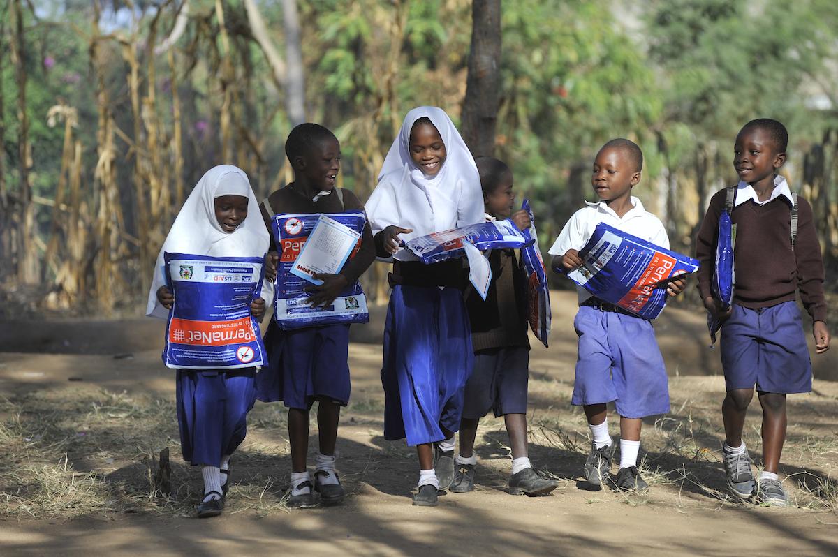 Children walk home after receiving bed nets at Iringo B primary school.