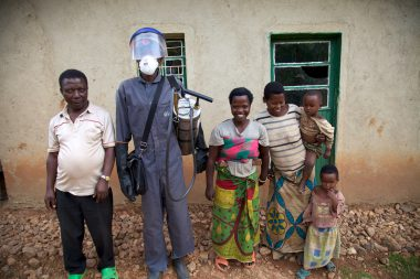 IRS spray operator with family during IRS campaign, Rwanda, 2014