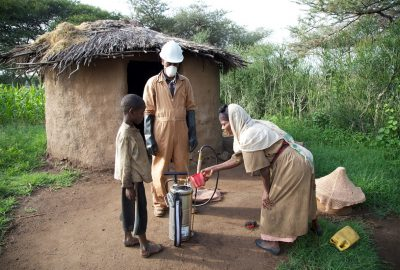 IRS spray operator outside house with family during IRS campaign, Ethiopia, 2014