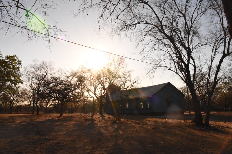 Sun shining down on a building in a rural landscape with trees in Zimbabwe