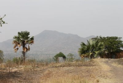 Ugandan landscape showing a dirt road, trees, house and mountain in the distance