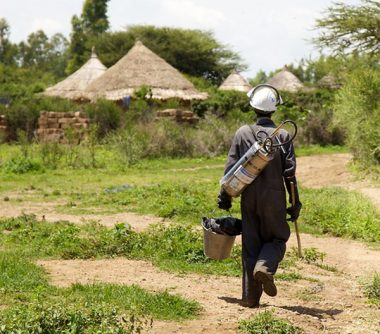 Man carrying indoor residual spraying equipment walking towards rural houses