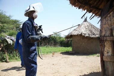 Man conducting indoor residual spraying of a rural African house